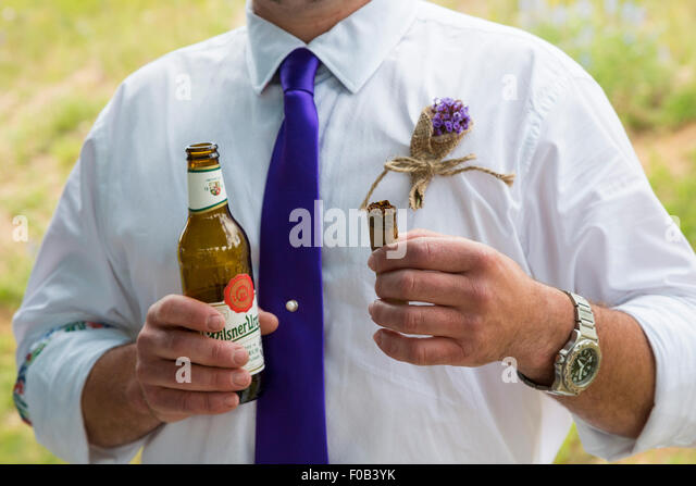 Dillon, Colorado - A man holds a beer and a cigar during a wedding ...
