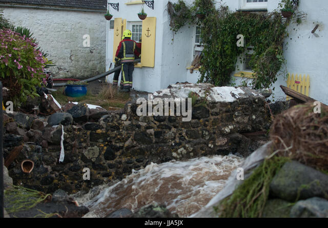 Coverack, Cornwall. 18th July 2017.  River beside local house being pumped rages after flash flood in coastal village - Stock Image