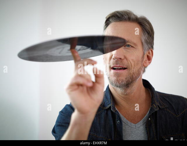 Mature man scrutinizing old vinyl record - Stock Image