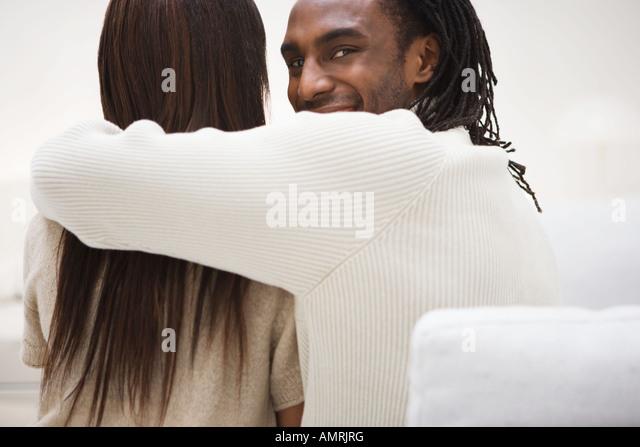 African man with arm around girlfriend - Stock-Bilder