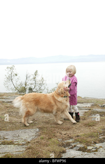 young girl with her golden retriever by lake - Stock Image