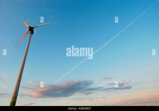 A wind turbine and a vapor trail in the sky - Stock Image