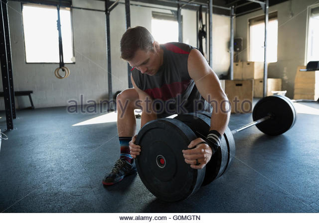 Man placing weightlifting plates on barbell in gym - Stock Image