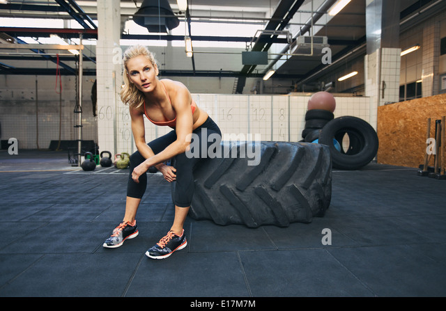 Fit young lady sitting on a big tire after her workout. Woman taking rest after exercise at gym. - Stock Image