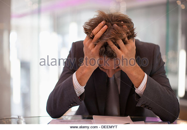 Frustrated businessman sitting at desk with  head in hands - Stock-Bilder