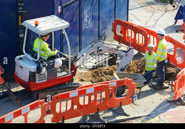 Three man team digging up pavement - Stock Image