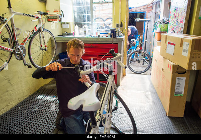 A worker adjusting repairing mending bike at Summit Cycles, small independent bicycle sales and repair centre Aberystwyth - Stock Image