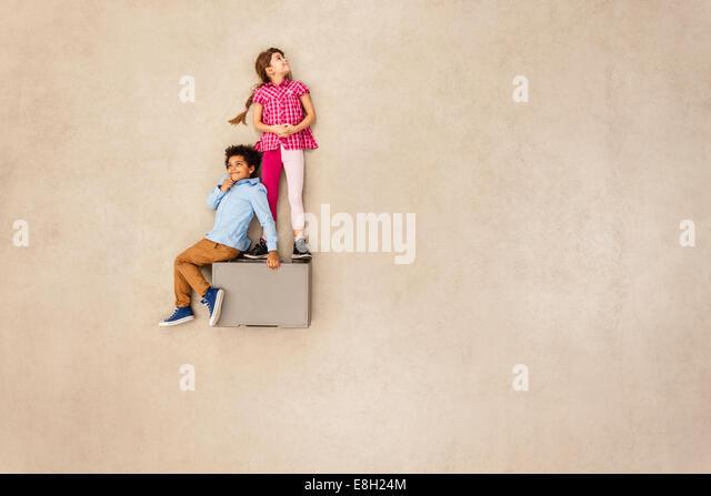 Boy and girl on box - Stock Image