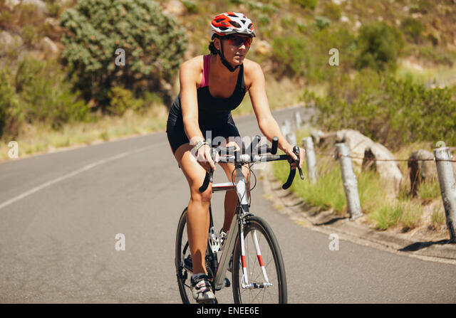 Young woman triathlon athlete cycling. Caucasian female athlete riding cycle on country road. - Stock Image