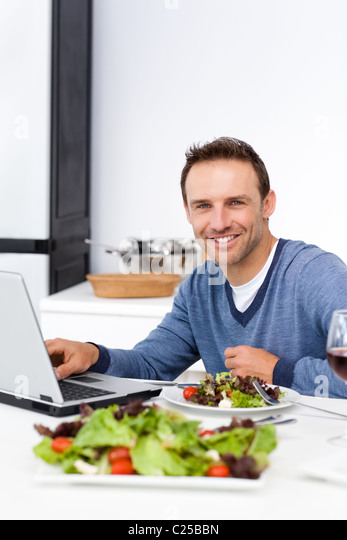 Cheerful man working on his laptop while having lunch - Stock-Bilder