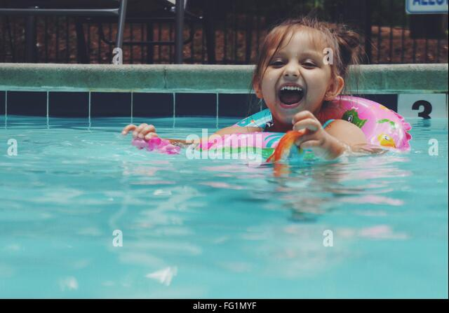 Portrait Of Cheerful Girl With Inflatable Ring In Swimming Pool - Stock Image