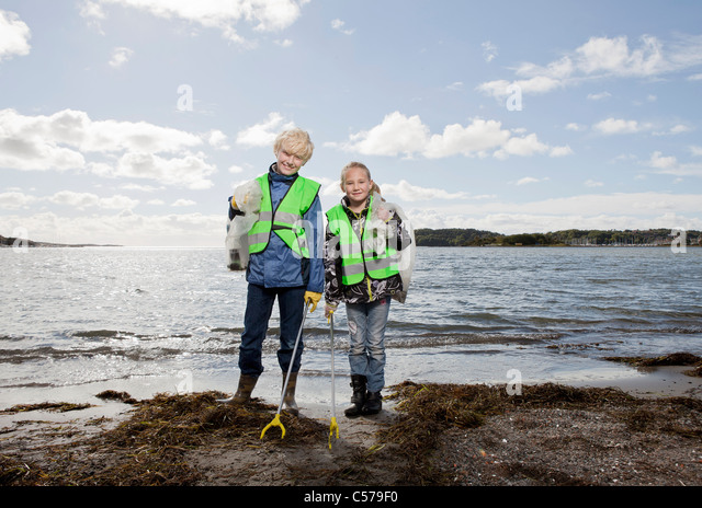 Children in safety vests cleaning beach - Stock Image