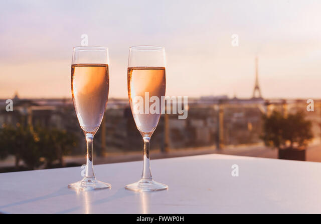 two glasses of champagne at rooftop restaurant with view of Eiffel Tower and Paris skyline, luxury romantic dinner - Stock Image