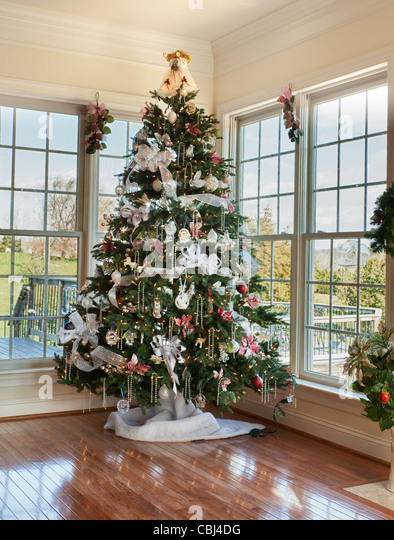 Christmas tree decorated with silver and white ribbons and ornaments in family home - Stock Image