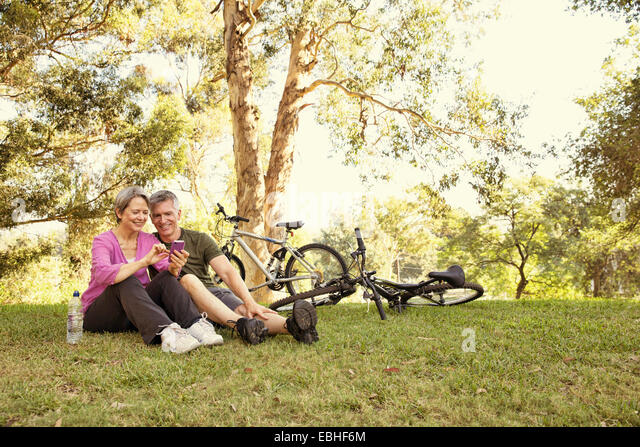 Mature cycling couple sitting in park looking at smartphone - Stock Image