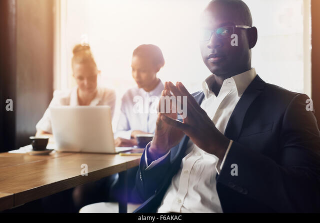 Serious black business man sitting in front of his employees at office - Stock Image