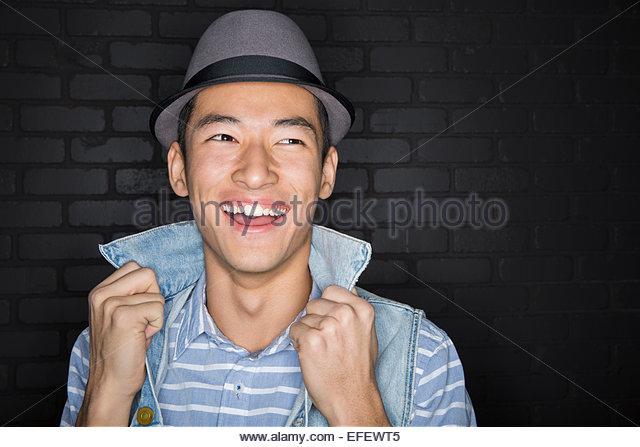 Portrait of laughing man wearing fedora - Stock Image