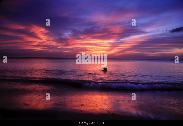Couple swimming at sunset Koh Lanta Thailand - Stock Image