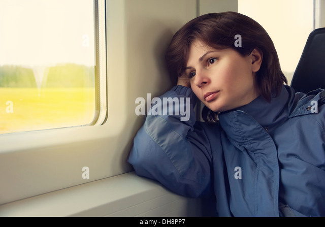 Young woman is traveling by train, looking to the window - Stock Image