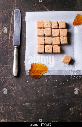 Fudge candy and caramel on baking paper, served with vintage knife over dark background. Top view - Stock Image