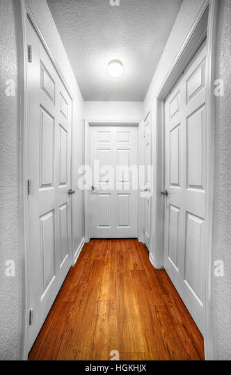 A hallway leads to four different doors, suggesting many choices. - Stock Image