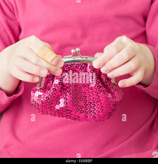 Hand of little girl holding pink change purse - Stock Image
