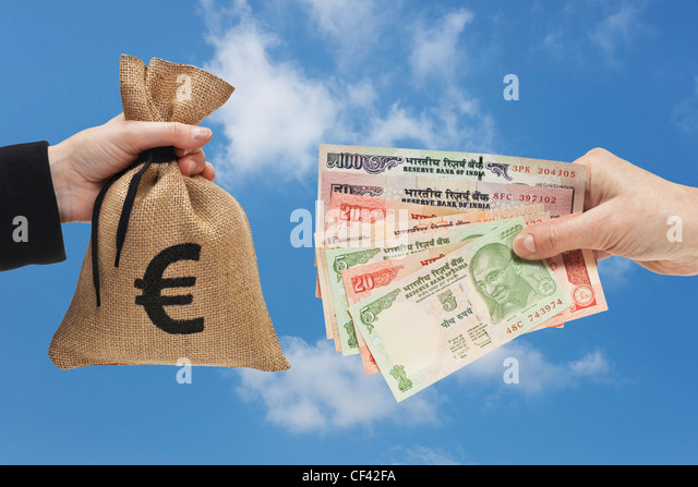 Many diverse Indian rupee bills are held in the hand. At the other side a is money bag with  Euro currency sign. - Stock-Bilder