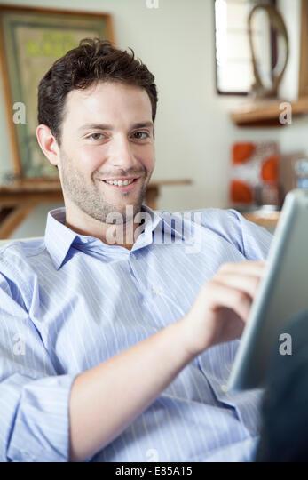 Man using digital tablet, smiling at camera - Stock-Bilder