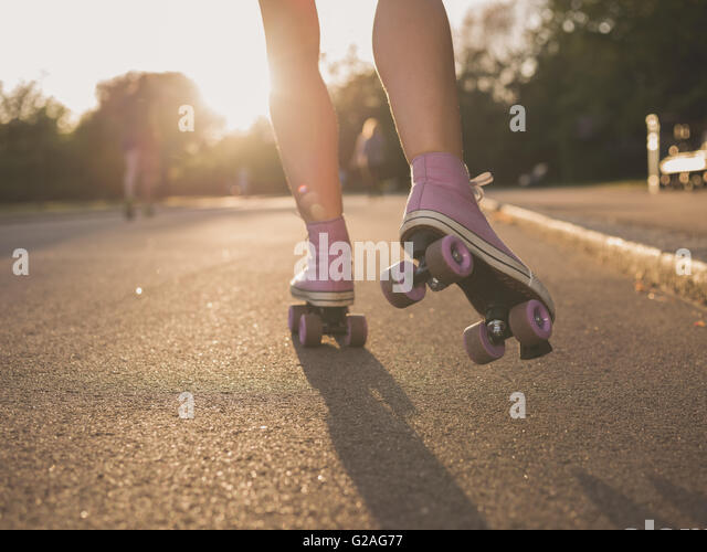 The legs of a young woman as she is roller skating in a park at sunset - Stock Image