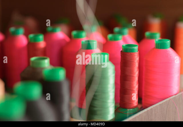 Red and green coloured threads in factory - Stock Image