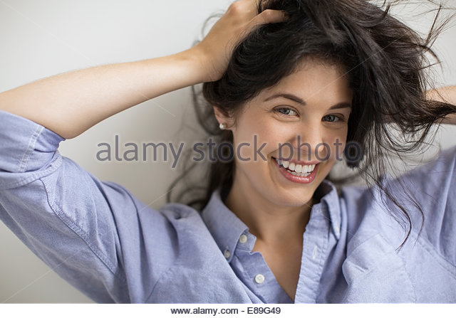 Portrait of woman with hands in hair - Stock Image