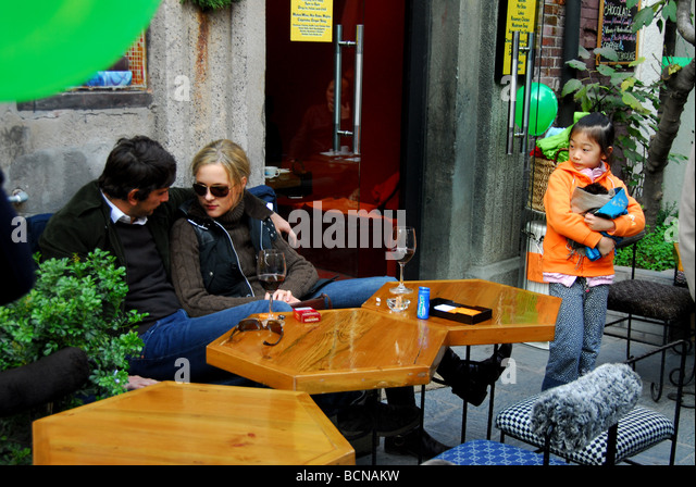 Foreign couple cuddling outside of a trendy restaurant on Taikang Artistic Lane while a Chinese young girl looking - Stock-Bilder