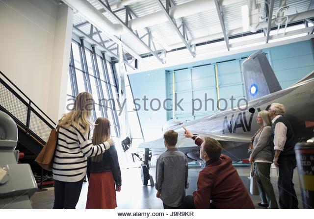 Multi-generation family looking up at airplanes in war museum hangar - Stock-Bilder
