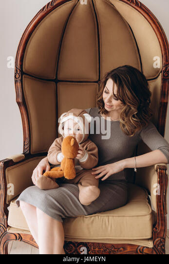 Caucasian mother sitting in armchair with baby son wearing bear costume - Stock-Bilder