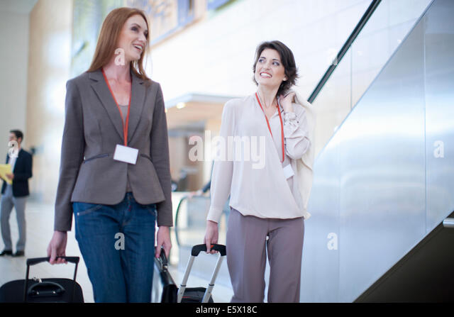 Two businesswoman arriving at conference centre - Stock Image