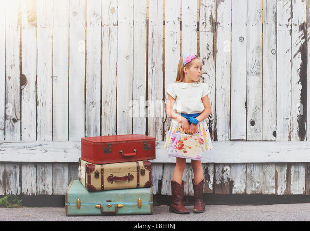 USA, Girl (6-70 standing by suitcases outdoors - Stock Image