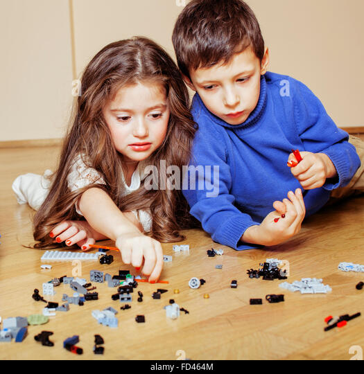 funny cute children playing lego at home, boys and girl smiling, first education role - Stock Image