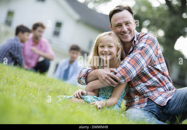 A father and daughter at a summer party sitting on  grass. - Stock Image
