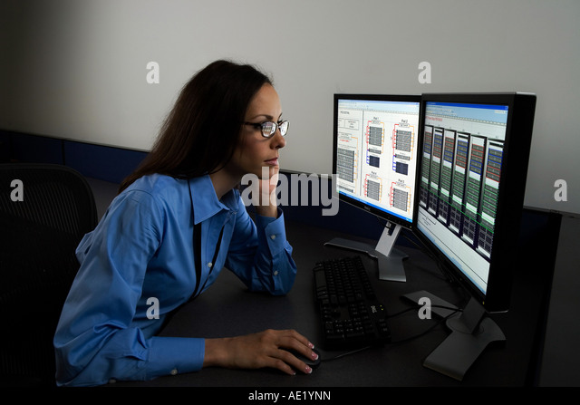 A woman sitting at a desk working on a two monitor computer system. - Stock Image