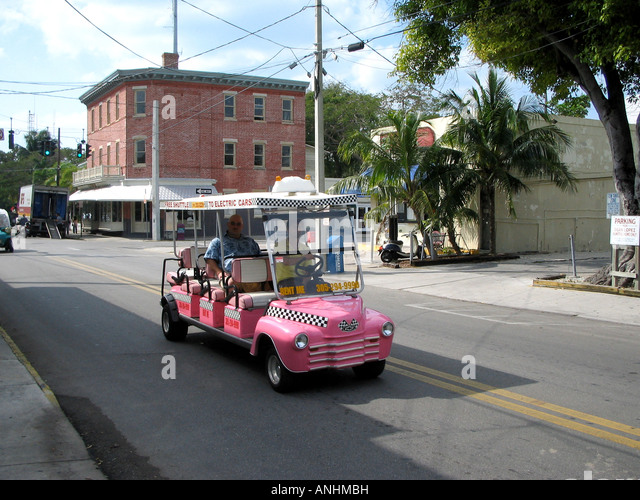 Florida Key West street with pink buggy car driver and tourist - Stock Image