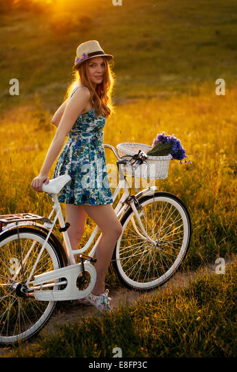 Young adult women standing with bicycle - Stock-Bilder