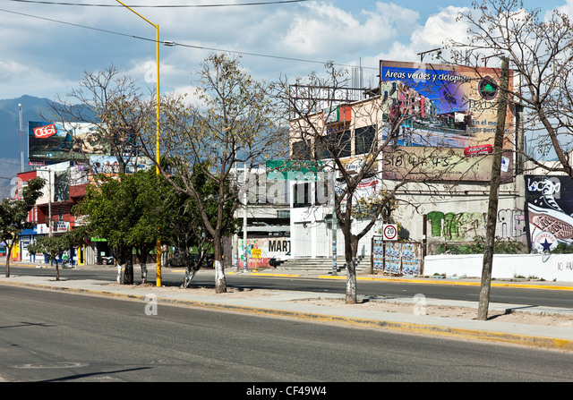 boulevard commercial strip in Oaxaca Mexico with colorful advertising billboards overshadowed by beauty of mountains - Stock Image
