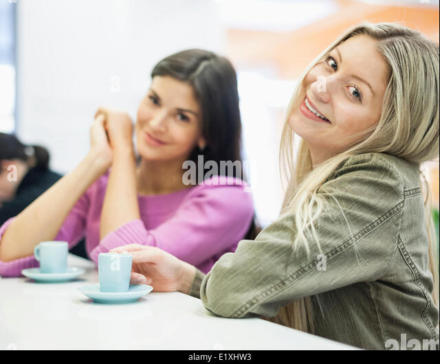 Portrait of young businesswomen smiling at cafeteria table - Stock-Bilder
