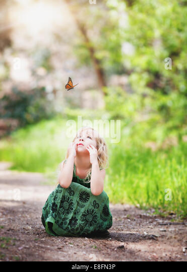 Girl (4-5) watching butterfly - Stock Image
