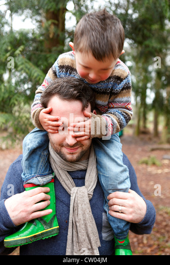 Father carrying son on shoulders - Stock-Bilder
