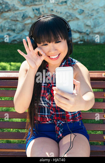 Asian woman taking self portrait selfie photo on park. She is happy - Stock Image