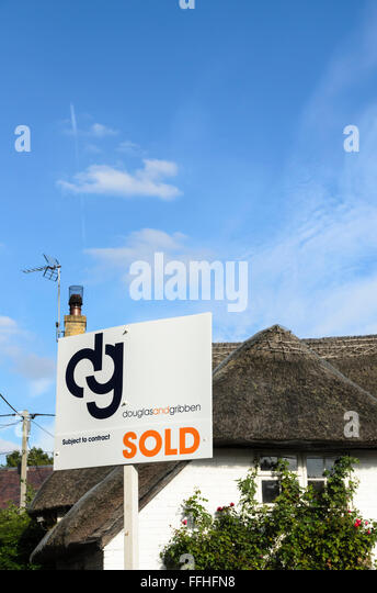 An estate agents sign outside a thatched cottage in Uffington, Oxfordshire, England, UK. - Stock Image