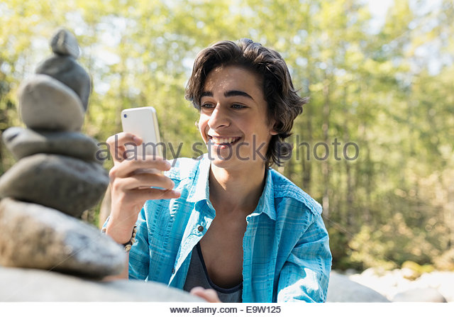 Teenage boy photographing stacked stones in woods - Stock Image