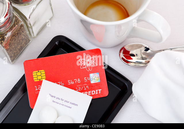 Photo of a credit card placed on a tray to pay for a restaurant bill. - Stock Image