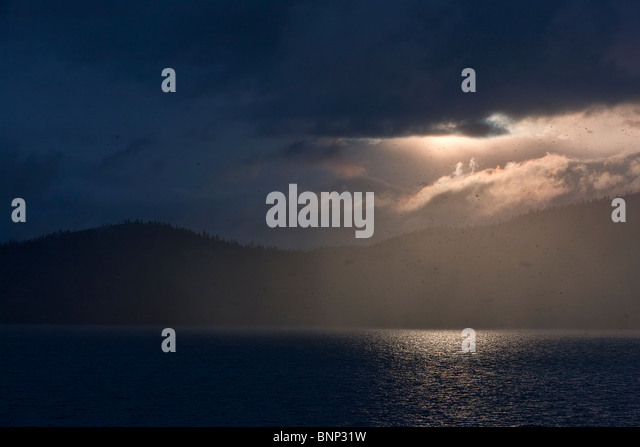 A light snow falls over Lake Tahoe as the setting sun warms the clouds, Lake Tahoe, Nevada, USA. - Stock Image